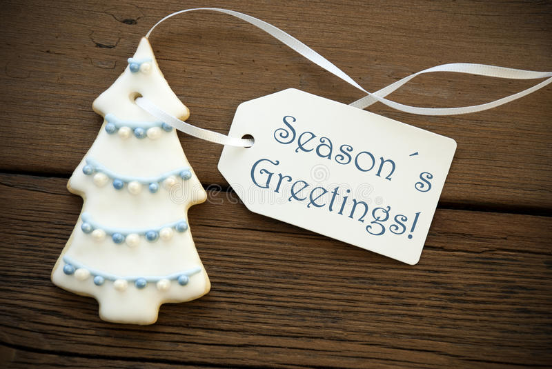 Blue Seasons Greetings on a Tag. Blue Words Seasons Greetings on a white Label on a Christmas Tree Cookie on Wood, Winter or Christmas Background stock photo