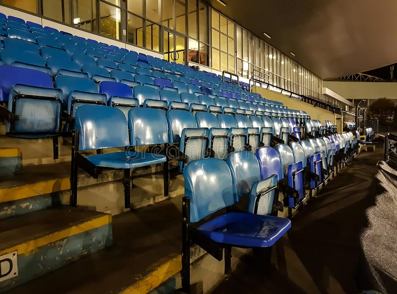 Blue Seats in the Stadium. A few rows of blue seats in a stadium at night royalty free stock image