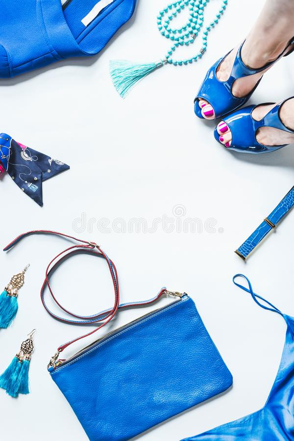 Blue set of woman fashionable clothes and accessories, top view. Blue outfit flat lay with female legs in pumps, handbag, jacket,. Jewelry and belt, top view royalty free stock images