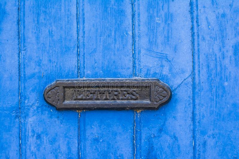 Blue shabby door with a vintage mailbox. Blue shabby door with french vintage mailbox royalty free stock photography