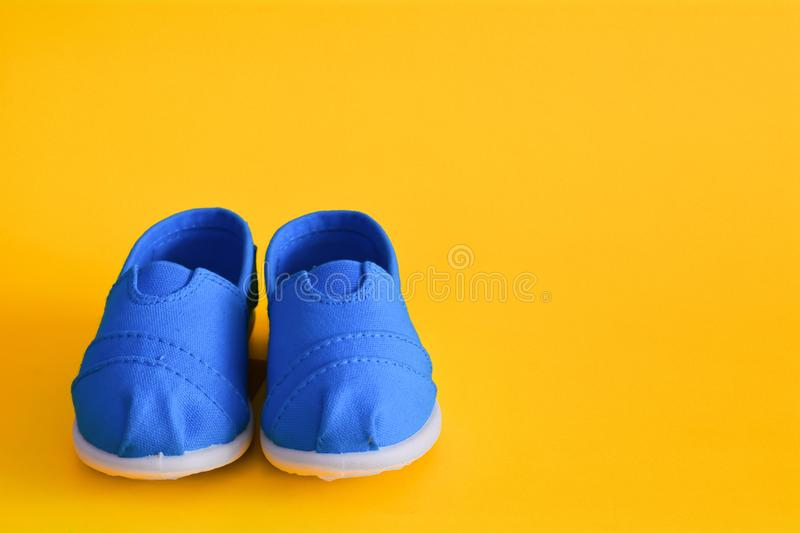 Blue shoes for children isolated. On a yellow background royalty free stock photo
