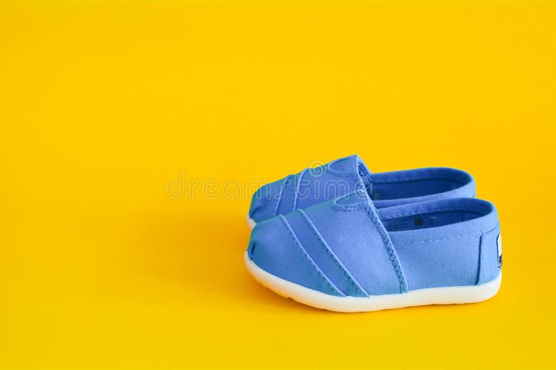 Blue shoes for children isolated. On a yellow background stock photo