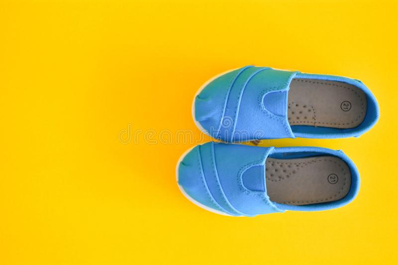Blue shoes for children isolated. On a yellow background stock photography