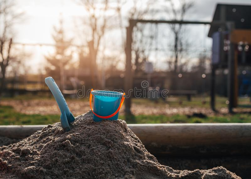 Blue shovel and bucket for children sticking in a mountain of sa stock images