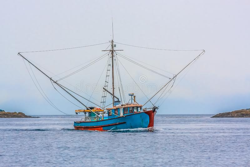 Blue Shrimp Boat on Grey Day. A blue shrimp boat trolling the grey waters of Alaska royalty free stock images