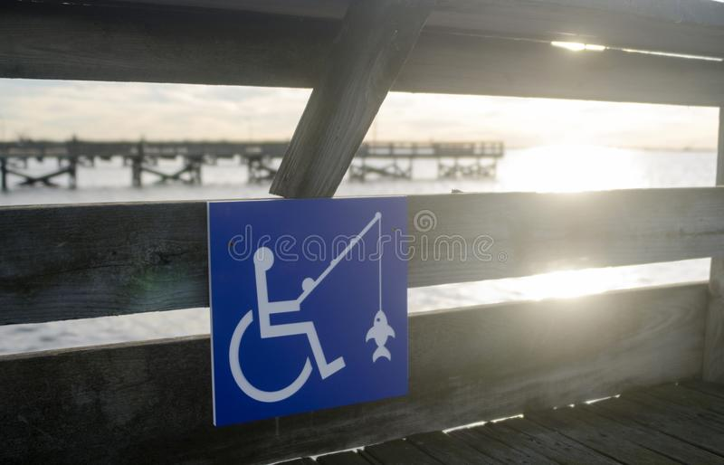 Blue fishing sign indicates wheelchair accessible on fishing pie stock photography