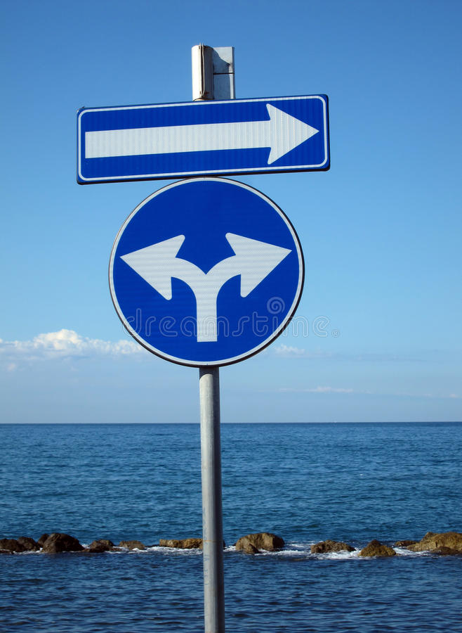 Blue signs for directions on background with sea and sky stock photography