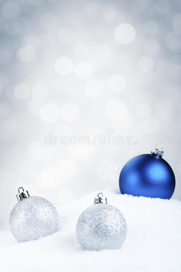 Blue and silver Christmas baubles on snow, silver background stock images