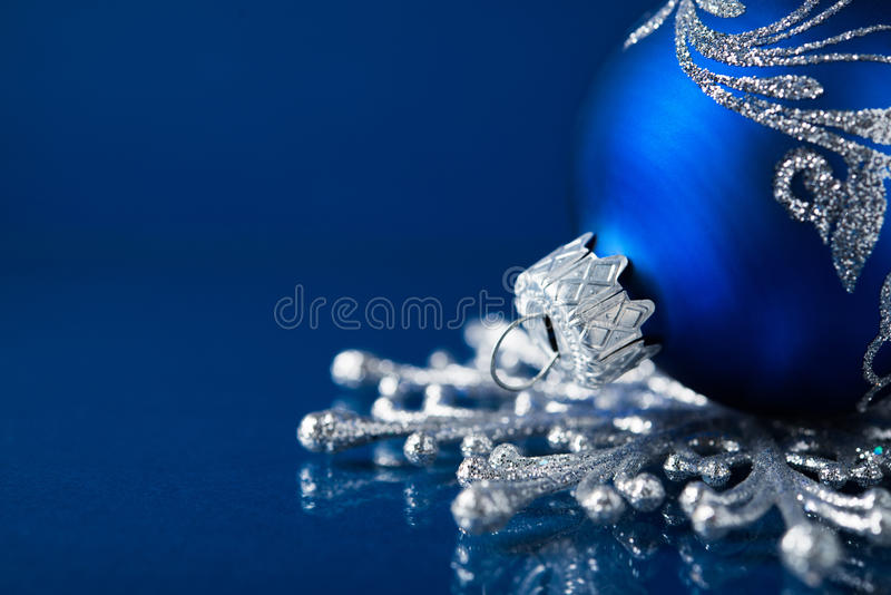 Blue and silver christmas ornaments on dark blue background stock photography