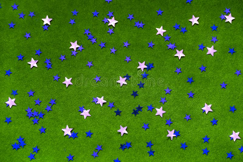 Blue and silver sparkles stars on a bright green background. stock image