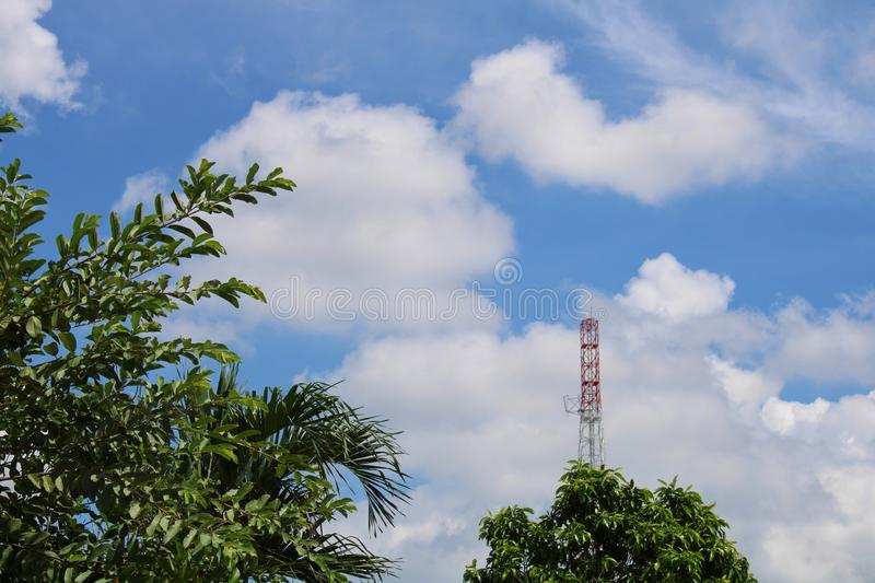 Blue skies with cloud and a green leaves of trees. Nature, background, abstract, tower, technology, white, sky, environment, season, summer, weather, editorial royalty free stock image