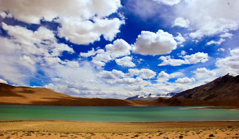 Blue skies over green lake stock photo