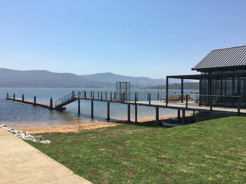 Private jetty onto a lagoon. Blue skies and a private dock, green grass and distant mountain views stock photography