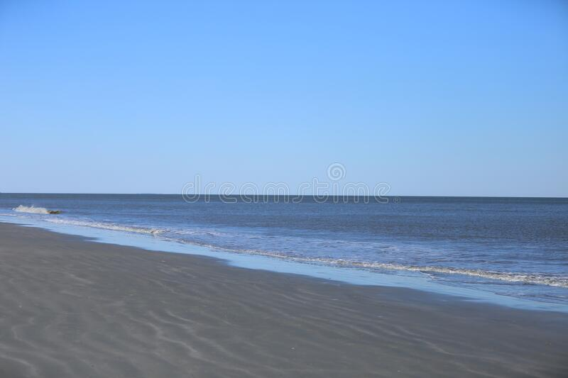 Blue skies and serene waves on Hilton Head Island, South Carolina sandy rippling beaches. Blue skies and crystal ocean with serene waves crashing on rippling royalty free stock images