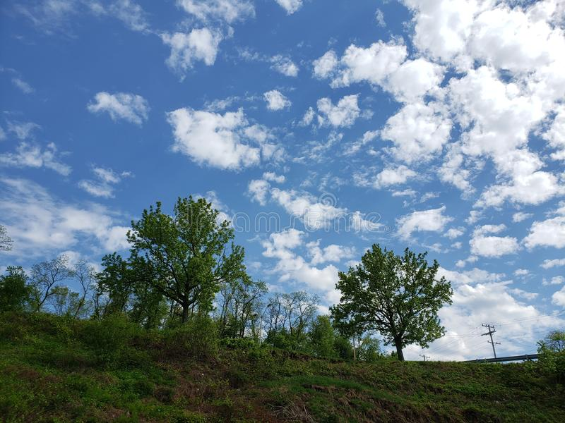 Blue skies with white clouds over a tree lined hill royalty free stock photo