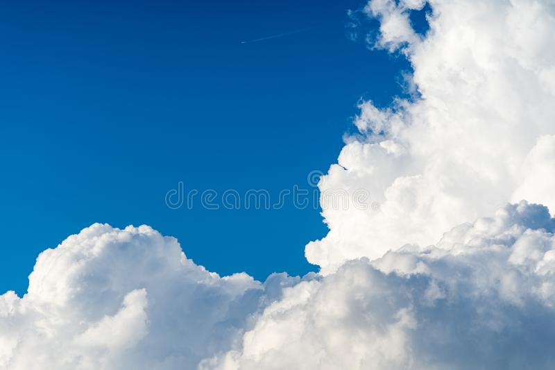 Blue sky airplane contrail white cumulus clouds before storm in summer. Airplane travels across the blue summer sky with high rising white cumulus clouds right stock photo