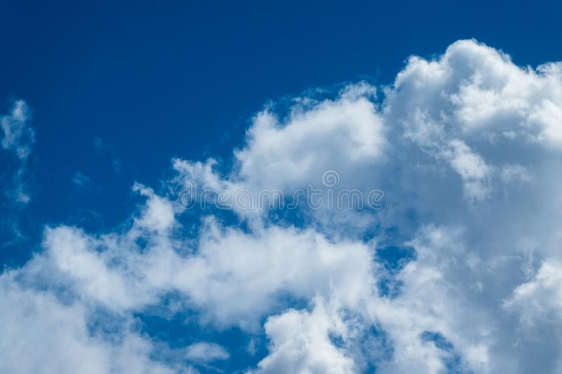 Blue sky background with fluffy white clouds stock images