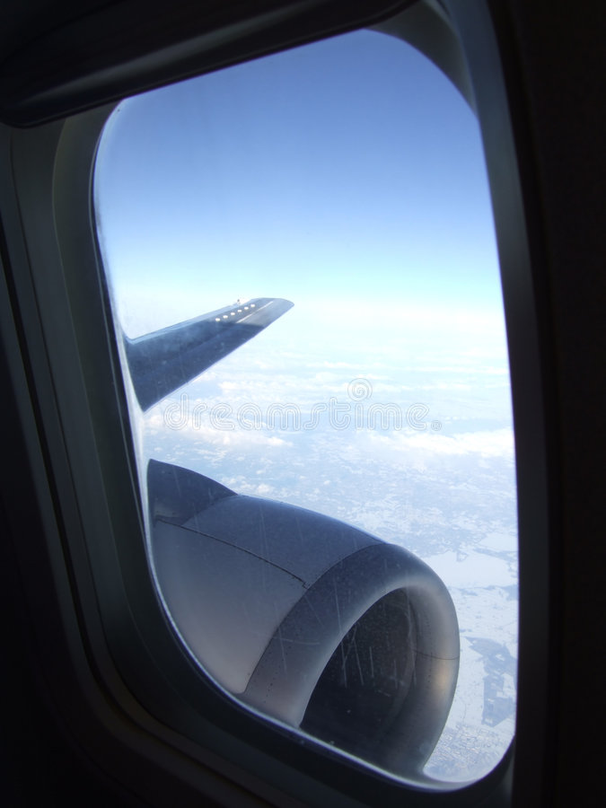 Blue sky behind plane window. Blue sky with nice white clouds, from a plaine window with visible wing and turbine royalty free stock photo