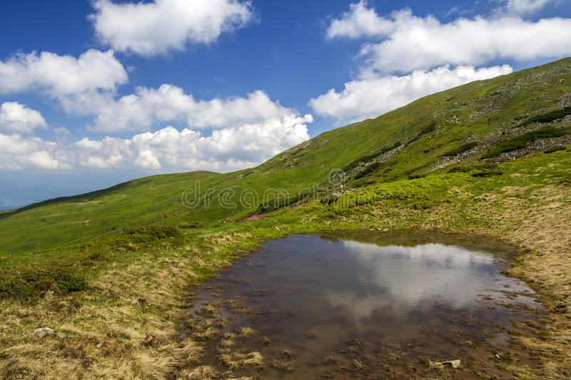 Blue sky with bright white clouds reflected in small lake between green hills on sunny day. Summer panorama royalty free stock photography