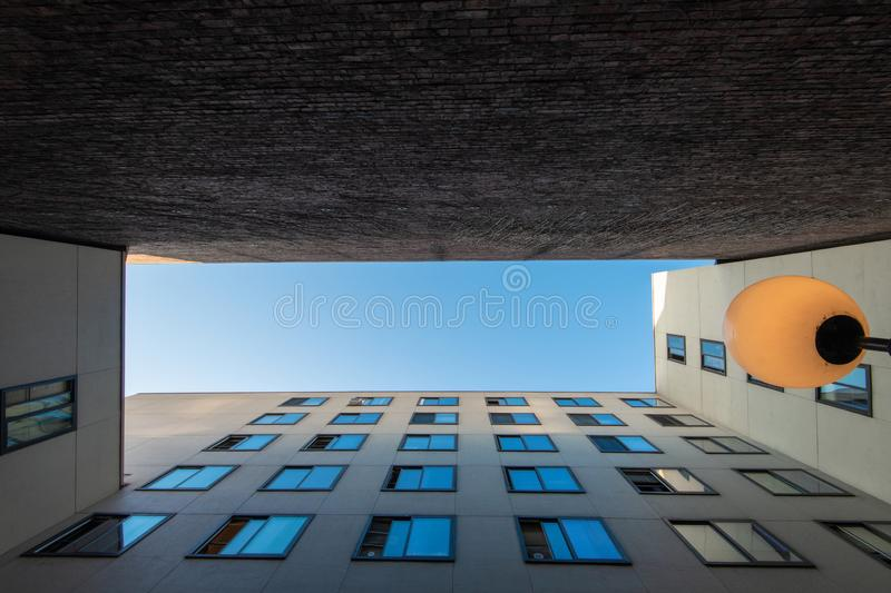 Blue sky between buildings with square windows royalty free stock images