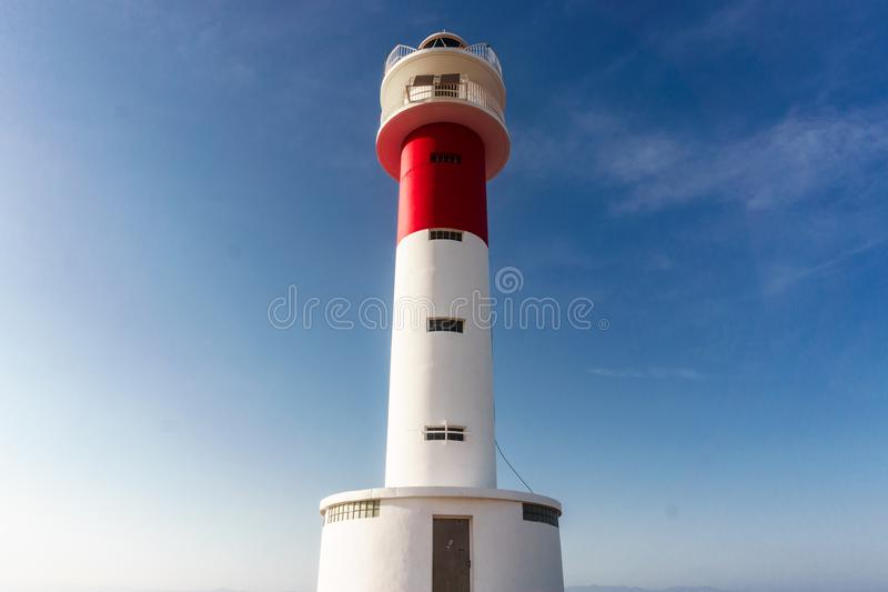 Close up of `Far del Fangar` lighthouse. Into Natural Park of Delta de l`ebre, Tarragona, Catalonia. Blue sky and clear, beautiful day to go to the beachblue royalty free stock photos