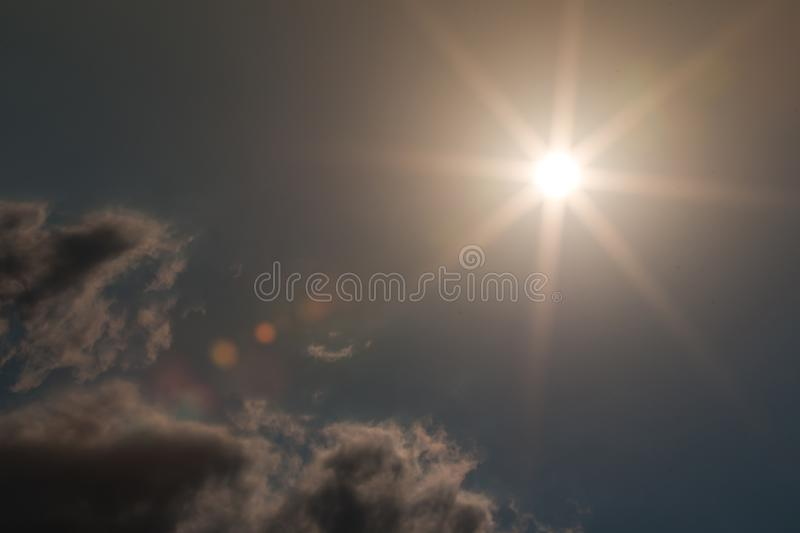 Big bright sun star flare background. Blue sky and cloud with bright sun star flare background. Summer sun during evening stock photo