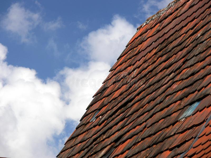 Blue sky with cloud and dark red brick roof stock photography