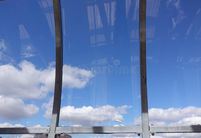 Blue sky with clouds behind curved glass.  stock images