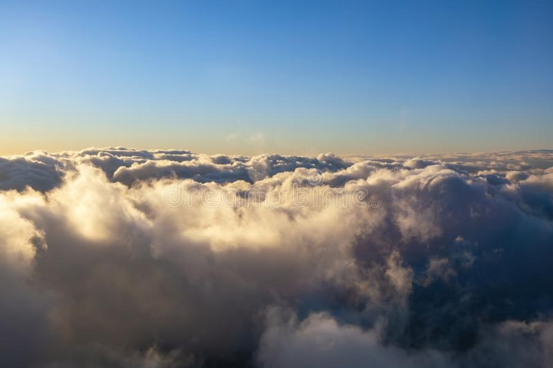 Above clouds colored by evening light. Blue sky and clouds colored by evening light stock image