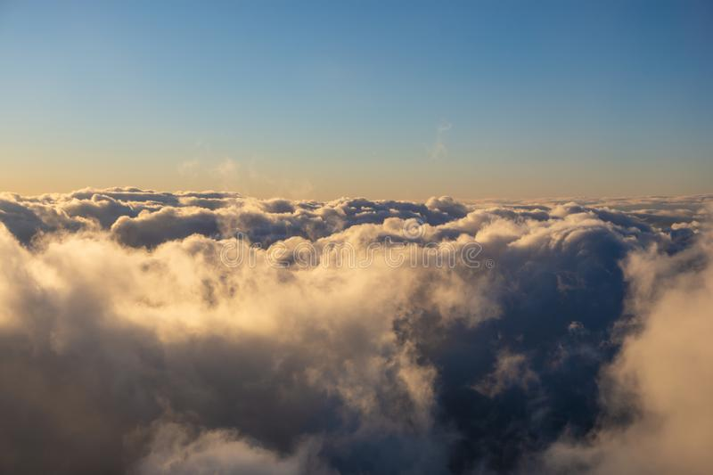 Above clouds colored by evening light. Blue sky and clouds colored by evening light stock images