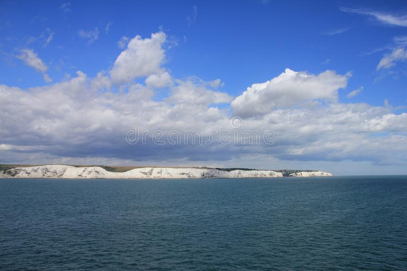 Blue sky with clouds and in the distance Dover in England in the summer. stock photography