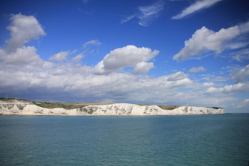Blue sky with clouds and in the distance Dover in England in the summer. royalty free stock photos