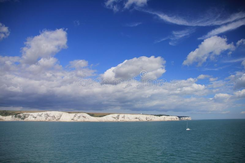 Blue sky with clouds and in the distance Dover in England in the summer. stock images