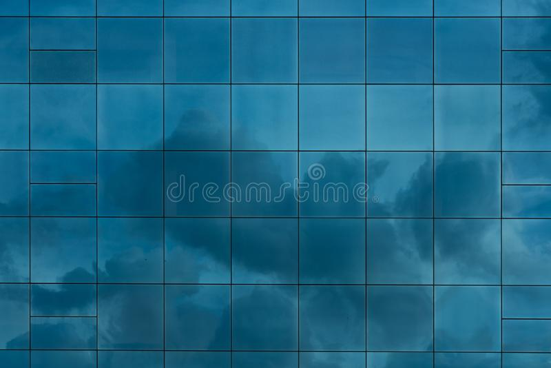 Blue sky with clouds. Mirrored in lots of square glass, background pattern stock photo