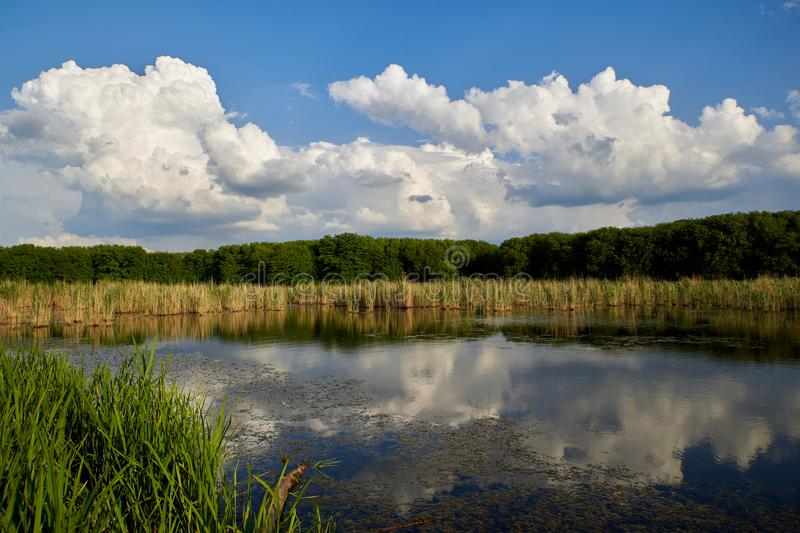 The blue sky and clouds are reflected in the calm waters of the lake stock images