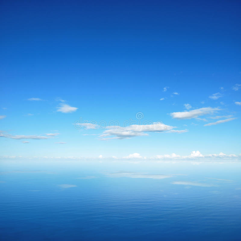 Blue sky and clouds with reflection on sea water royalty free stock photography
