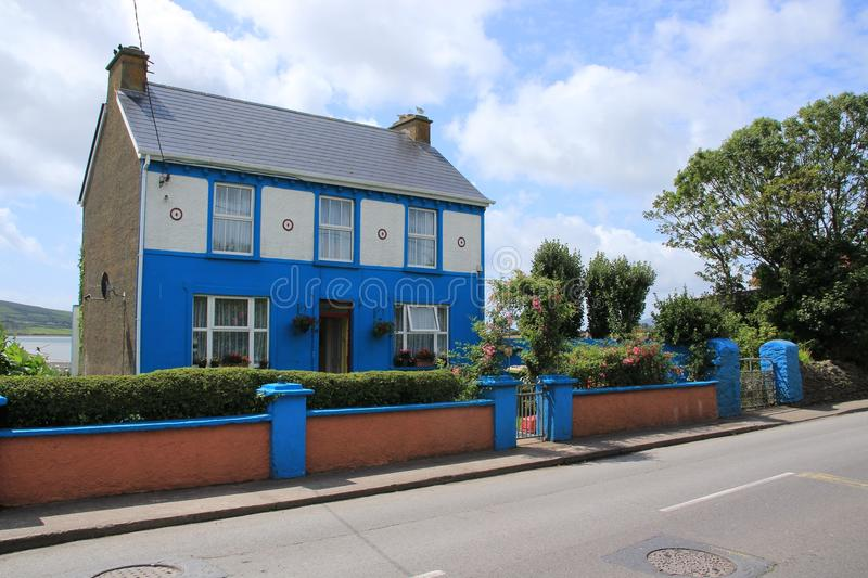 Blue sky with clouds and a striking blue house in the village Dingle in county Kerry in Ireland in the summer. stock photo