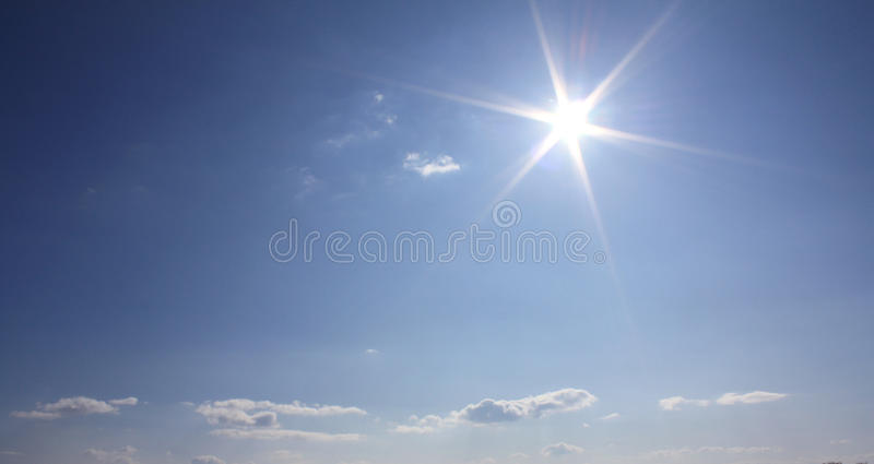 Blue sky clouds and sun. Winter sky with sun and clouds royalty free stock photo