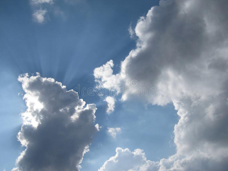 Blue sky clouds and sun rays stock photos