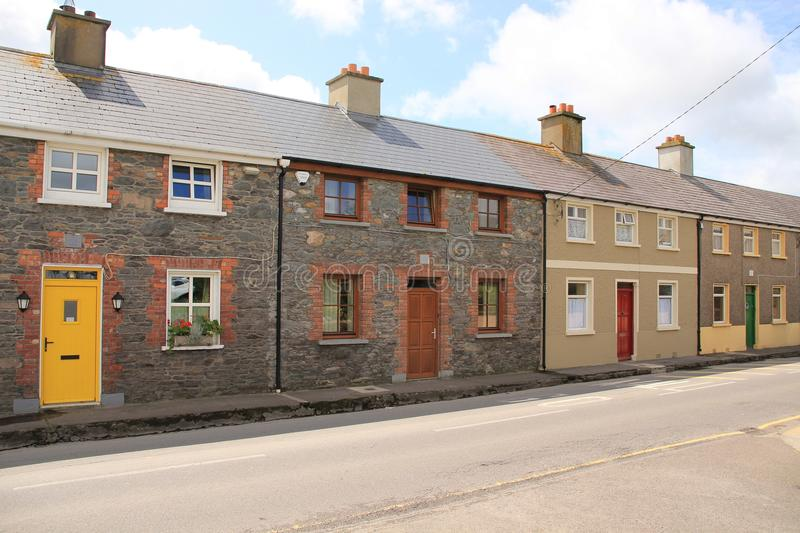 Blue sky with clouds and terraced houses in the village Dingle in county Kerry in Ireland in the summer. stock photos