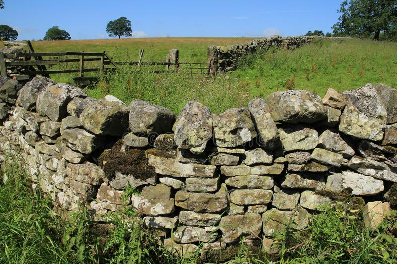Closed fence and a large dry stone wall in the summer. Blue sky with clouds, trees, a closed fence and an old large dry stone wall at the countryside in England royalty free stock photos