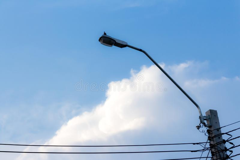 Blue sky cloudy abstract background,Black Lamp post and  wire power stock images