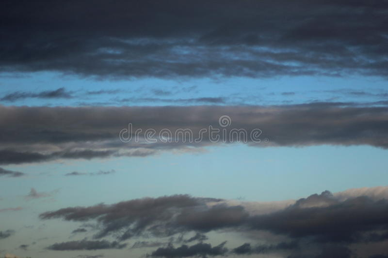 Blue sky with dark clouds stock image