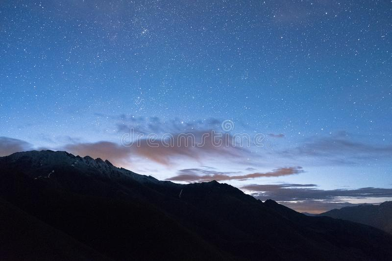 Blue sky at dawn with stars and a cloud above a mountain peak stock photo
