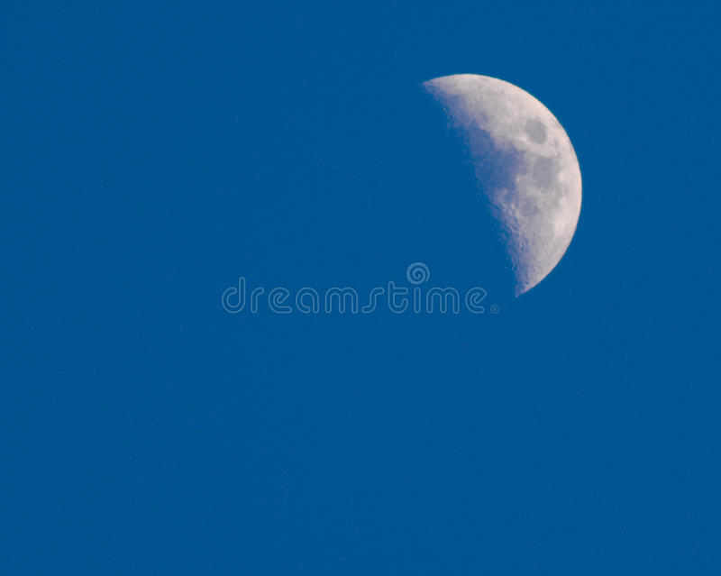 Blue sky daytime half moon. Moon shot at daytime with 300mm lens against a bright blue sky royalty free stock images