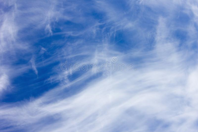 Blue sky and feathery clouds stock photo