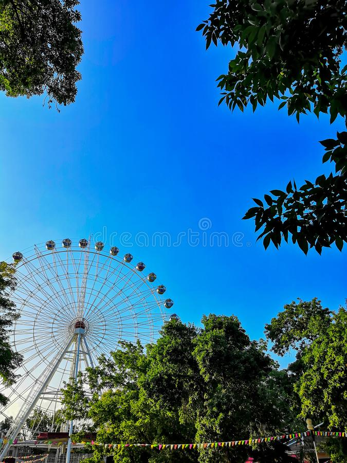 Blue sky Ferris wheel and green trees. Ferris wheel on blue sky background. Ferris wheel attraction in summer park. Orange metallic construction of attraction stock images