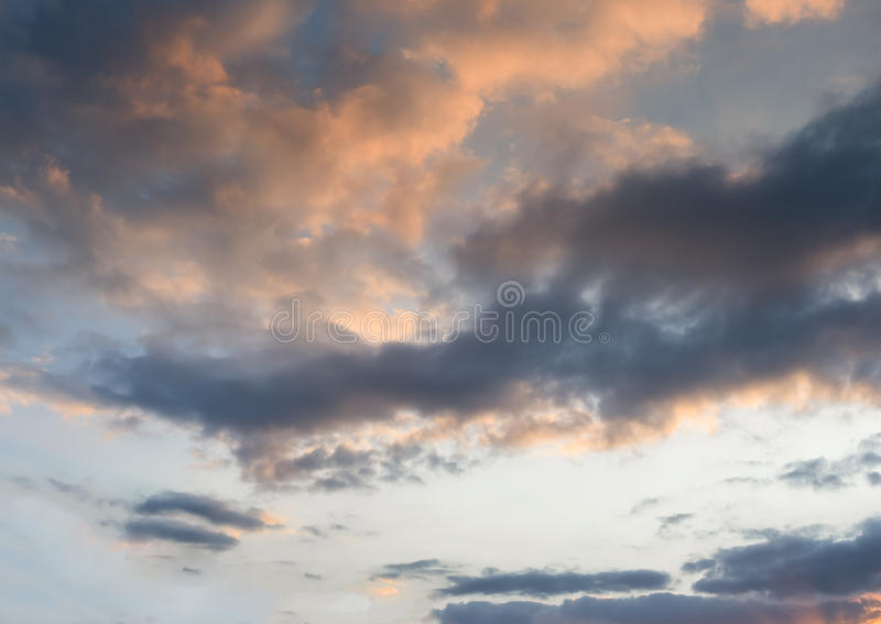The blue sky with golden fluffy clouds stock image