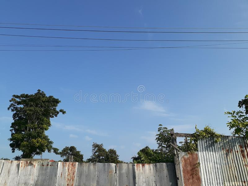 Blue Sky And Grung Corrugated Metal Sheets Below stock photo