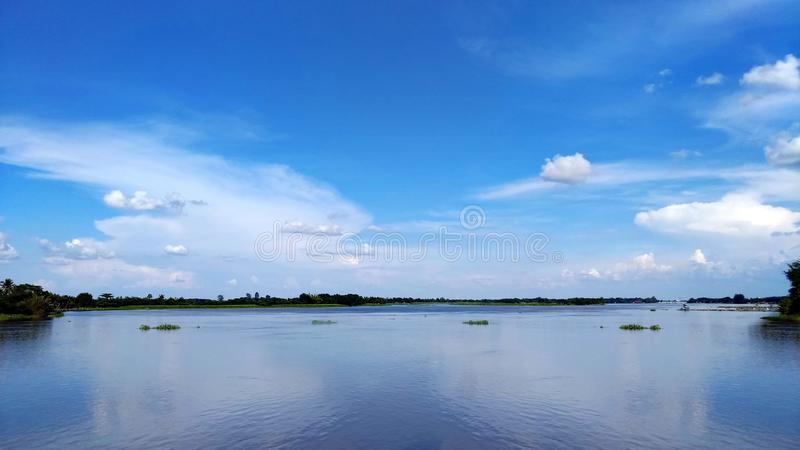 The blue sky has beautiful clouds reflecting on the river.  stock photos